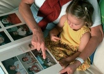 woman-and-child-looking-at-photo-album-photo-420x420-ts-78247677
